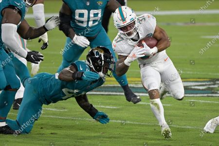 Miami Dolphins running back Myles Gaskin, right, runs past Jacksonville Jaguars defensive end K'Lavon Chaisson, left, during the first half of an NFL football game, in Jacksonville, Fla
