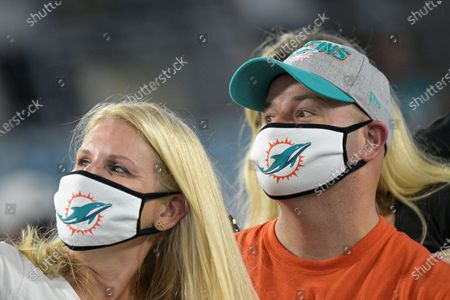 Fans watch the first half of an NFL football game between the Jacksonville Jaguars and the Miami Dolphins, in Jacksonville, Fla