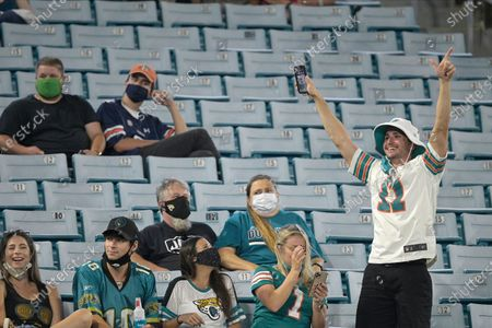 Maimi Dolphins fan, right, cheers as his team scores against the Jacksonville Jaguars during the first half of an NFL football game, in Jacksonville, Fla