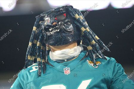 Jacksonville Jaguars fan in a mask cheers during the first half of an NFL football game against the Miami Dolphins, in Jacksonville, Fla