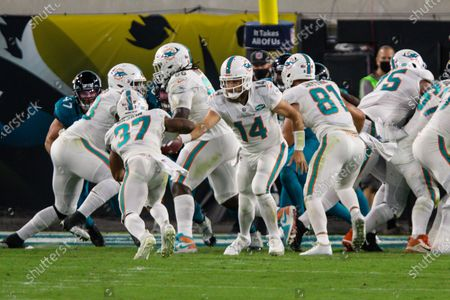Miami Dolphins quarterback Ryan Fitzpatrick (14) hands off the ball to running back Myles Gaskin (37) during the first half of an NFL football game against the Jacksonville Jaguars, in Jacksonville, Fla
