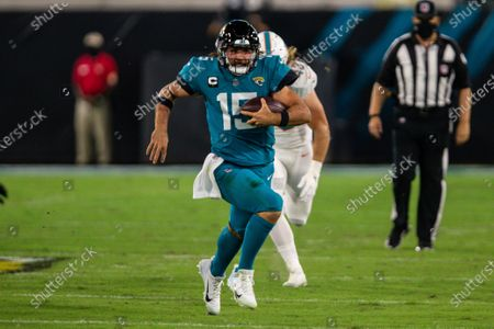 Jacksonville Jaguars quarterback Gardner Minshew (15) runs the ball for a first down during the first half of an NFL football game against the Miami Dolphins, in Jacksonville, Fla