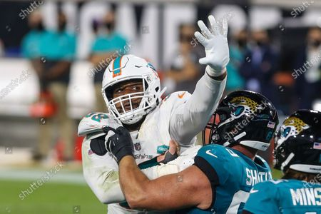 Miami Dolphins defensive tackle Raekwon Davis (98) rushes the passer blocked by Jacksonville Jaguars center Tyler Shatley (69) during the second half of an NFL football game, in Jacksonville, Fla. Dolphins won 31-13