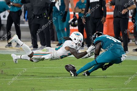 Miami Dolphins strong safety Bobby McCain, left, breaks up a pass intended for Jacksonville Jaguars wide receiver Chris Conley during the second half of an NFL football game, in Jacksonville, Fla