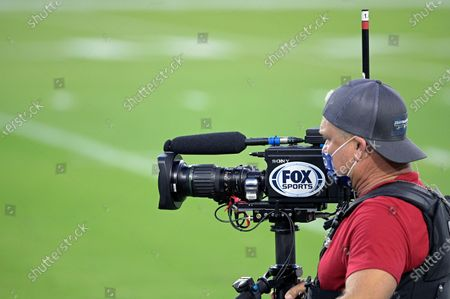 Fox Sports television cameraman works from the field during warmups before an NFL football game between the Jacksonville Jaguars and the Miami Dolphins, in Jacksonville, Fla