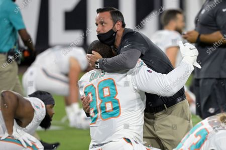 Miami Dolphins linebackers coach Anthony Campanile hugs defensive tackle Raekwon Davis (98) during warmups before an NFL football game against the Jacksonville Jaguars, in Jacksonville, Fla