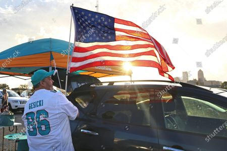 Terry Mohr of Brooklyn, N.Y. hoists a flag as he tailgates with friends before an NFL football game between the Jacksonville Jaguars and the Miami Dolphins, in Jacksonville, Fla