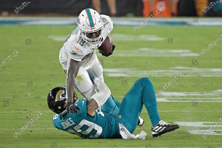 Stock Photo of Jacksonville Jaguars strong safety Josh Jones, left, brings down Miami Dolphins wide receiver Preston Williams (18) after a reception during the second half of an NFL football game, in Jacksonville, Fla