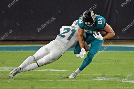 Stock Picture of Miami Dolphins safety Eric Rowe (21) tackles Jacksonville Jaguars tight end Tyler Eifert (88) after a reception during the second half of an NFL football game, in Jacksonville, Fla