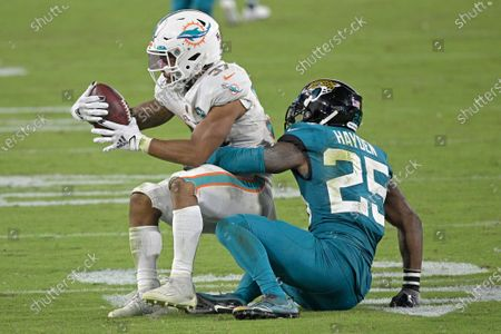 Miami Dolphins running back Myles Gaskin (37) is stopped by Jacksonville Jaguars cornerback D.J. Hayden (25) during the second half of an NFL football game, in Jacksonville, Fla