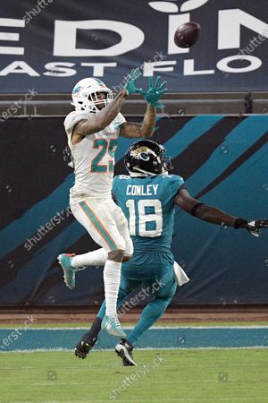 Miami Dolphins cornerback Xavien Howard, left, intercept a pass intended for Jacksonville Jaguars wide receiver Chris Conley (18) during the second half of an NFL football game, in Jacksonville, Fla