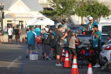 Fans tailgate outside of TIAA Bank Field during before an NFL football game between the Jacksonville Jaguars and the Miami Dolphins, in Jacksonville, Fla