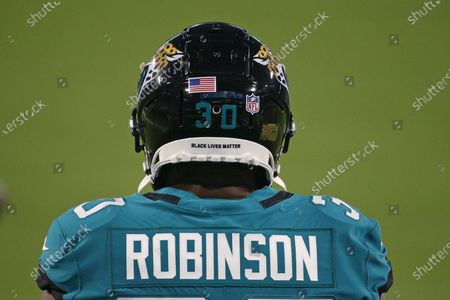 Jacksonville Jaguars running back James Robinson takes the field for warmups with the phrase Black Lives Matter on the back of his helmet before an NFL football game against the Miami Dolphins, in Jacksonville, Fla