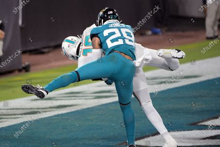 Miami Dolphins wide receiver Preston Williams, back left, catches a pass in the end zone of a touchdown as Jacksonville Jaguars strong safety Josh Jones (29) tires to defend during the first half of an NFL football game, in Jacksonville, Fla
