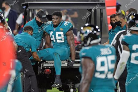 Teammates watch as Jacksonville Jaguars outside linebacker Leon Jacobs (48) is taken off the field after he was injured during the first half of an NFL football game against the Miami Dolphins, in Jacksonville, Fla