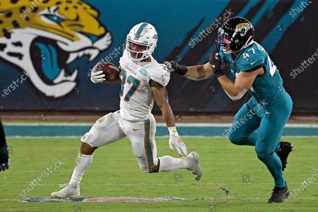 Miami Dolphins running back Myles Gaskin, left, runs past Jacksonville Jaguars middle linebacker Joe Schobert (47) during the first half of an NFL football game, in Jacksonville, Fla