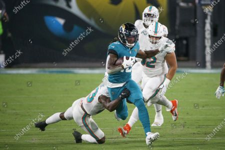 Jacksonville Jaguars wide receiver Laviska Shenault Jr., center, runs for yardage after a reception before being tackled by Miami Dolphins cornerback Noah Igbinoghene during the first half of an NFL football game, in Jacksonville, Fla