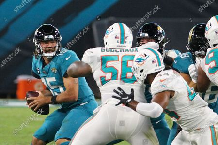 Miami Dolphins defensive tackle Davon Godchaux (56) pressures Jacksonville Jaguars quarterback Gardner Minshew, left, as he looks for a receiver during the first half of an NFL football game, in Jacksonville, Fla