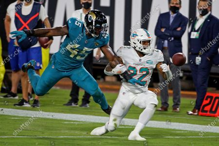 Jacksonville Jaguars defensive end K'Lavon Chaisson (45) is called for pass interference as he grabs Miami Dolphins running back Matt Brenda (22) during the first half of an NFL football game, in Jacksonville, Fla