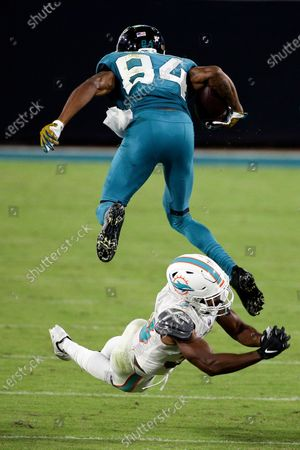 Jacksonville Jaguars wide receiver Keelan Cole (84) leaps over Miami Dolphins cornerback Jamal Perry during the second half of an NFL football game, in Jacksonville, Fla