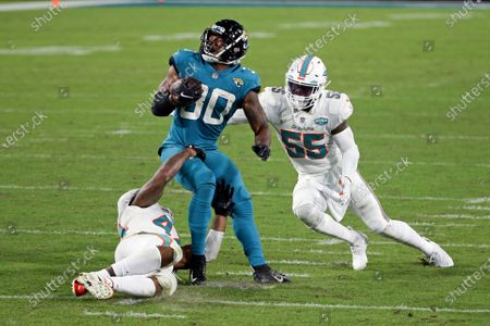 Jacksonville Jaguars running back James Robinson, center, looks for a way to get past Miami Dolphins outside linebacker Elandon Roberts, left, and outside linebacker Jerome Baker (55) during the second half of an NFL football game, in Jacksonville, Fla