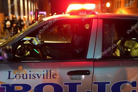 Police officer observes protesters, in Louisville, Ky. Authorities pleaded for calm while activists vowed to fight on Thursday in Kentucky's largest city, where a gunman wounded two police officers during anguished protests following the decision not to charge officers for killing Breonna Taylor