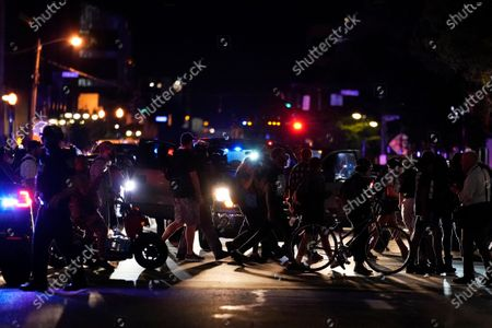 Protesters march, in Louisville, Ky. Authorities pleaded for calm while activists vowed to fight on Thursday in Kentucky's largest city, where a gunman wounded two police officers during anguished protests following the decision not to charge officers for killing Breonna Taylor