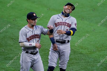 Houston Astros' Alex Bregman, left, and Carlos Correa laugh before the team's baseball game against the Texas Rangers in Arlington, Texas