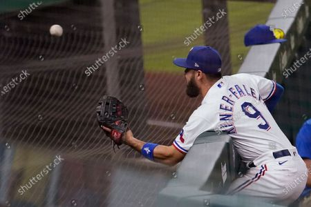 Texas Rangers third baseman Isiah Kiner-Falefa reaches over the wall but can't get to a foul ball hit by Houston Astros' Michael Brantley during the eighth inning of a baseball game in Arlington, Texas
