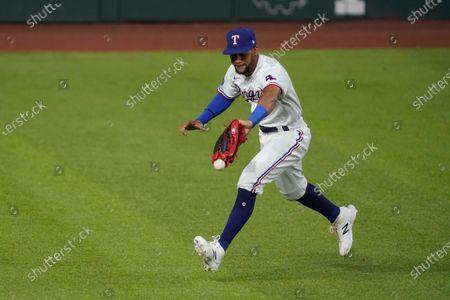 Texas Rangers center fielder Leody Taveras drops a ball, hit by Houston Astros' Kyle Tucker, for an error during the first inning of a baseball game in Arlington, Texas