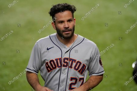 Houston Astros' Jose Altuve walks to the dugout after scoring on a triple by Alex Bregman during the first inning of the team's baseball game against the Texas Rangers in Arlington, Texas