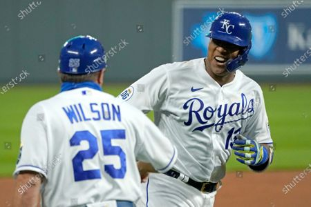 Kansas City Royals' Salvador Perez celebrates with third base coach Vance Wilson after hitting a three-run home run during the first inning of the team's baseball game against the Detroit Tigers, in Kansas City, Mo
