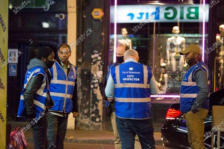 City inspectors patrol the streets of Soho in central London on the first day of the 10PM curfew comes into force. Prime Minister Boris Johnson has announced new measures to attempt to reduce the rising number of new Covid-19 infections.