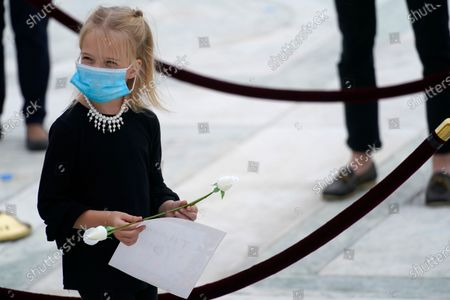 A child wears a face mask as mourners pay respects as Justice Ruth Bader Ginsburg lies in repose under the Portico at the top of the front steps of the U.S. Supreme Court building, in Washington. Ginsburg, 87, died of cancer on Sept. 18.