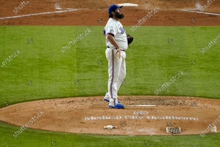 Texas Rangers starting pitcher Lance Lynn (35) pauses on the mound as he works against the Houston Astros in a baseball game in Arlington, Texas