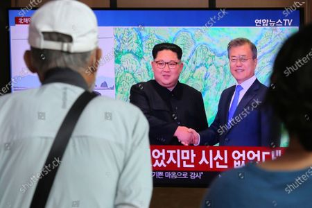 """People watch a TV showing a file image of North Korean leader Kim Jong Un, left, and South Korean President Moon Jae-in during a news program at the Seoul Railway Station in Seoul, South Korea, . North Korean leader Kim apologized Friday over the killing of a South Korea official near the rivals' disputed sea boundary, saying he's """"very sorry"""" about the incident he called unexpected and unfortunate, South Korean officials said"""