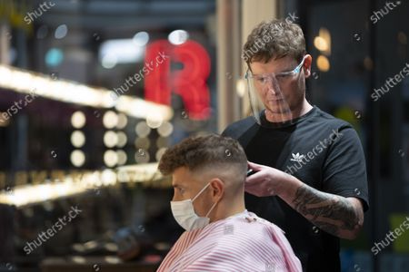 A man wearing a mask has his hair cut in Manchester, Britain, on Sept. 24, 2020. British Prime Minister Boris Johnson on Sept. 22 announced new restrictive measures to tackle a sharp rise in the country's coronavirus cases. Johnson confirmed that from Thursday, all pubs, bars and restaurants in England must operate a table service only -- except for takeaways -- and will be forced to close at 10:00 p.m. BST (2100 GMT).