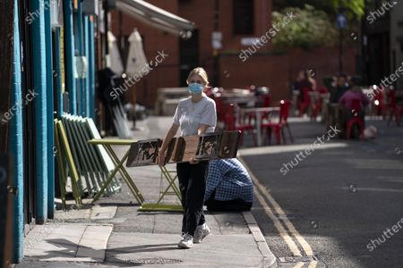 A staff worker puts out a bench outside a cafe in Manchester, Britain, on Sept. 24, 2020. British Prime Minister Boris Johnson on Sept. 22 announced new restrictive measures to tackle a sharp rise in the country's coronavirus cases. Johnson confirmed that from Thursday, all pubs, bars and restaurants in England must operate a table service only -- except for takeaways -- and will be forced to close at 10:00 p.m. BST (2100 GMT).