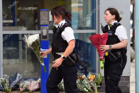 Police officers lay floral tributes outside Croydon Custody Centre following the death of a police officer