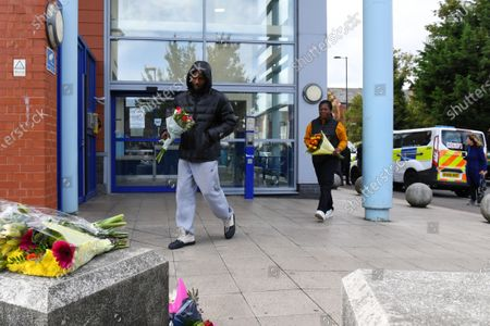 People lay floral tributes outside Croydon Custody Centre following the death of a police officer