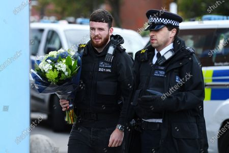 Officers lay floral tributes outside Croydon Custody Centre following the death of a police officer