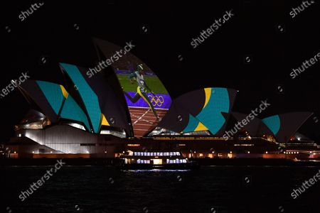 Stock Photo of A projection of Cathy Freeman is displayed on the Sydney Opera House in Sydney, Australia, 25 September 2020. Vision of the Cathy Freeman's 400-metre gold medal run at the 2000 Olympics has been projected onto the Sydney Opera House sails in honor of the 20th anniversary of her win.