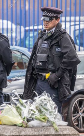 Police officers guard flowers outside Croydon Police Station in South London where a custody sergeant was shot dead inside the station last night. The Shooter who turned the gun on himself has survived and was taken to hospital in critical condition.