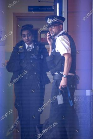 Police guard a crime scene after a Met Police Officer has been shot dead at Croydon Custody Centre on Windmill Lane in west London. A man, 23, is also critically ill in hospital with a gunshot wound - heaving shot himself thereafter.