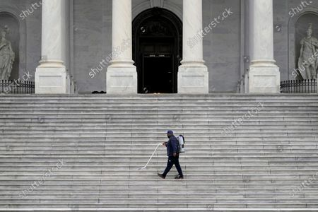Jason Jones with the Architect of the Capitol's Office, sweeps the Capitol steps for the arrival of Justice Ruth Bader Ginsburg, who will lie in state at the U.S. Capitol, in Washington. Ginsburg will be the first woman to lie in state at the Capitol