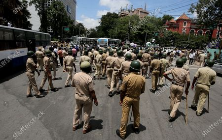 Indian policmen stand guard as members of different trade unions and farmers organizations protest against the central government for introducing new agri-ordinances, in Bangalore, India, 25 September 2020. Over hundreds of Farmers took to the street in protest rally is to show their support to the 'Bharat Bandh' and demanding central government to rollback in three agri-ordinances and the changes proposed in the Electricity Act, APMC and adequate compensation for the farmers who lost their life in floods.