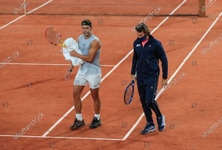 Spain's Rafael Nadal, left, and his coach Francisco Roig wearing a face mask to prevent the spread of coronavirus walk on the clay during practicing at the Roland Garros stadium in Paris, . Already repeatedly trimmed, crowd sizes for the French Open have been reduced again to just 1,000 spectators per day because of the worsening coronavirus epidemic in Paris
