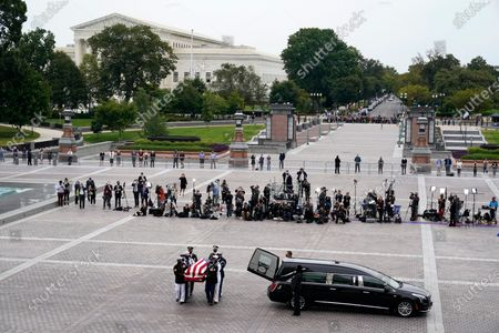 Stock Image of With the U.S. Supreme Court building in the background, the flag-draped casket of Justice Ruth Bader Ginsburg is carried by a joint services military honor guard to lie in state at the U.S. Capitol, in Washington