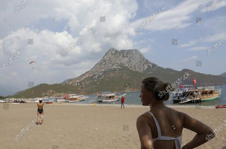 People watch as a Russian tourist and a Turkish instructor land on the beach after paragliding, in the Olympos area, about 100 kilometers west of Antalya, Turkey