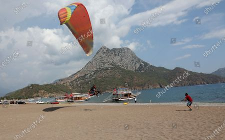 Russian tourist and a Turkish instructor land in the beach during a paragliding lesson in Adrasan in Olympos area, about 100 kilometers west of Antalya, Turkey, . With summer drawing to a close, Turkey is counting the Mediterranean costs with a warm weather after a tough year that saw a big cut deep into the country's crucial tourism sector
